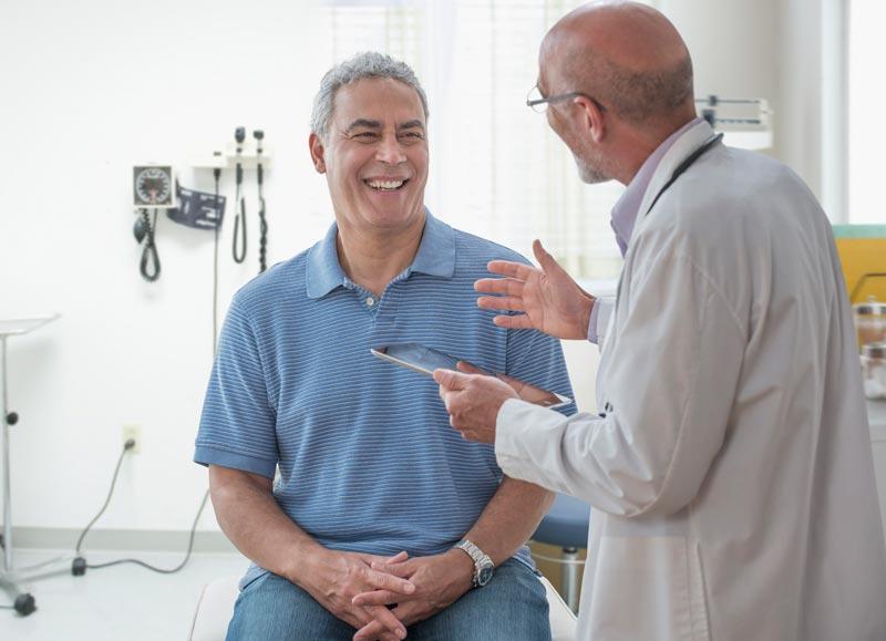 Doctor masculino hablando con paciente masculino sonriente