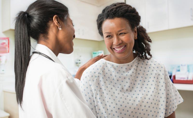 Doctora hablando con paciente sonriente