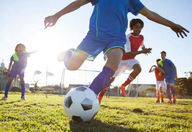 kids athletes playing soccer kicking soccer ball